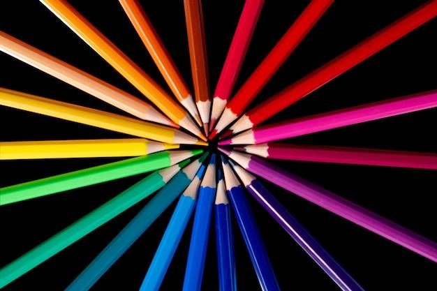 Muchos lápices de diferentes colores reflejados en negro