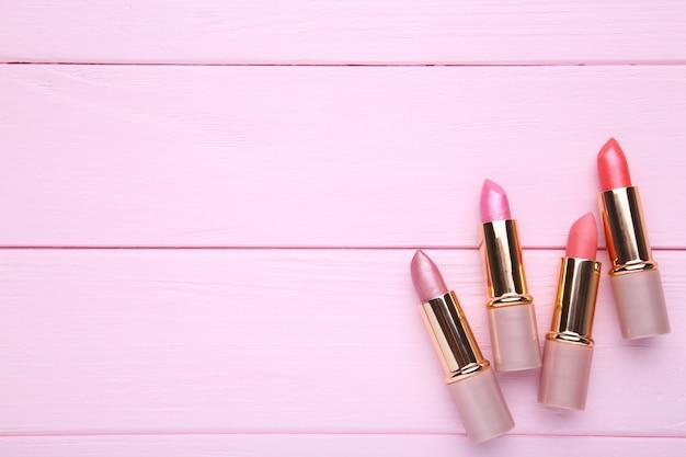 Muchos lápices labiales de color rosa sobre fondo rosa, de cerca
