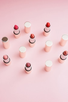 Muchos lápices labiales dorados de lujo en diferentes tonos de rosa