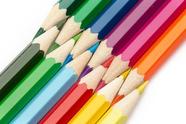 Muchos lápices de madera de colores sobre blanco