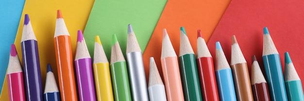 Muchos lápices multicolores sobre fondo de colores brillantes