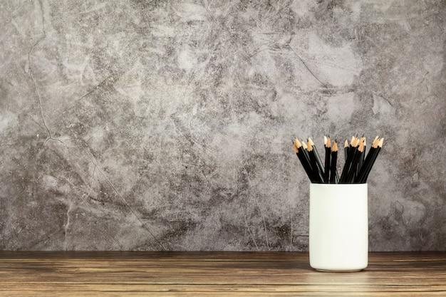 Muchos lápices en una taza de cerámica blanca en el escritorio de madera viejo en oficina