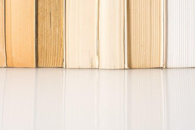 Muchos libros apilados con fondo blanco con espacio