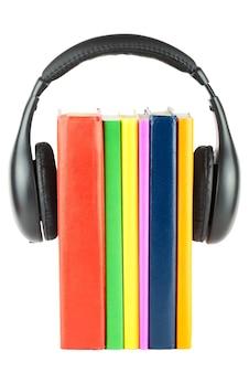 Muchos libros con auriculares sobre el fondo blanco.