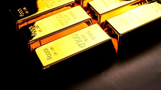 Muchos lingotes de oro que brillan sobre la mesa.