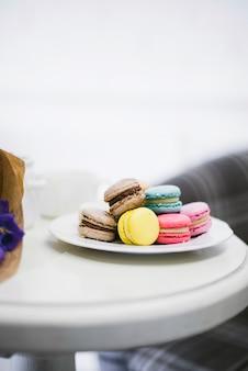 Muchos macarrones de colores en el plato de cerámica blanca sobre la mesa