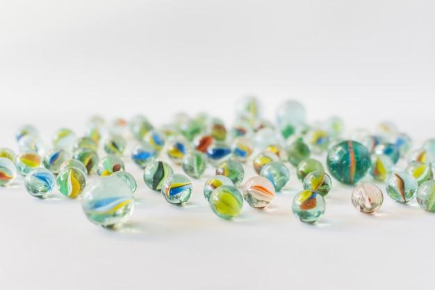 Muchos mármoles transparentes coloridos en el fondo blanco