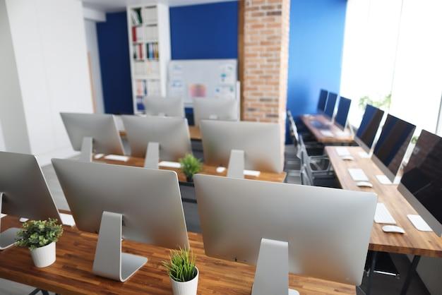 Muchos monitores plateados están parados sobre una mesa de madera en primer plano de la oficina. concepto de educación profesional de programador