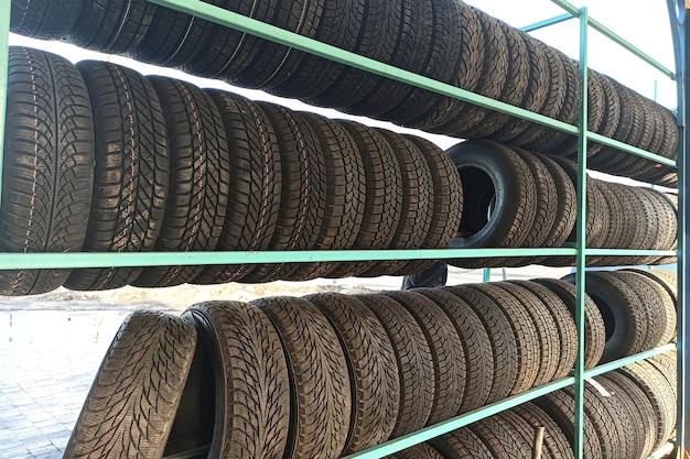Muchos neumáticos de caucho negro en el estante de la tienda para la venta.