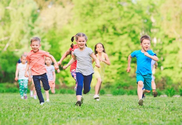 Muchos niños, niños y niñas diferentes corriendo en el parque en un día soleado de verano en ropa casual
