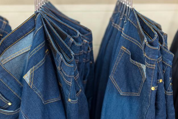 Muchos pantalones vaqueros de mezclilla colgando en un estante