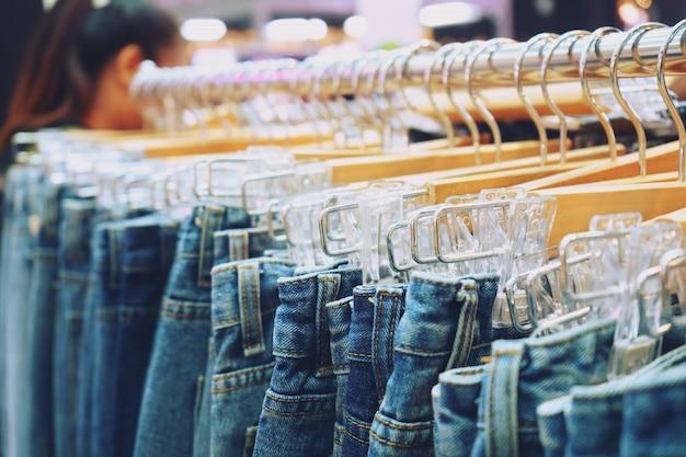 Muchos pantalones vaqueros que cuelgan en un estante en una tienda