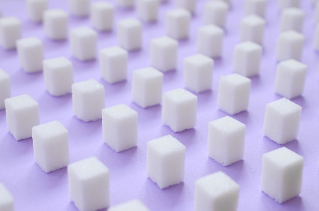 Muchos pequeños cubos de azúcar se alinean sobre un fondo violeta.