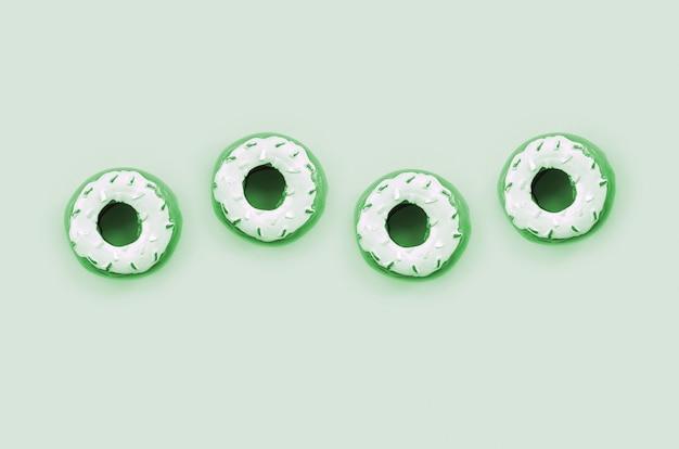 Muchos pequeños donuts de plástico se encuentra en un fondo de colores pastel