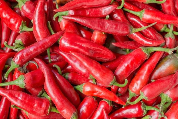 Muchos pimientos rojos maduros como fondo natural para verduras