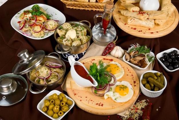 Muchos platos de comida en la mesa del restaurante. de cerca.
