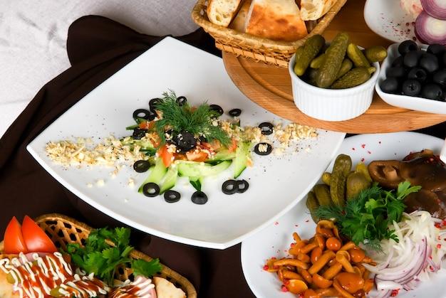 Muchos platos de comida en la mesa del restaurante. plato de ensalada de cerca