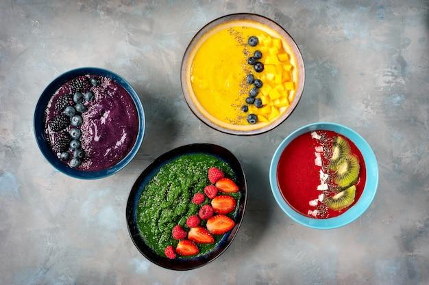 Muchos platos con frutas coloridas, batido viendo desde arriba.