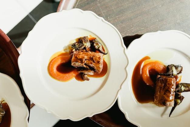 Muchos platos de lomo de cerdo confitados con alcachofas y jugosa salsa servidos por camareros.