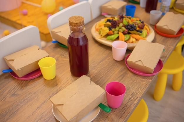 Muchos recipientes de comida para llevar caja de pizza tazas de café y bolsas de papel sobre fondo gris claro para ...