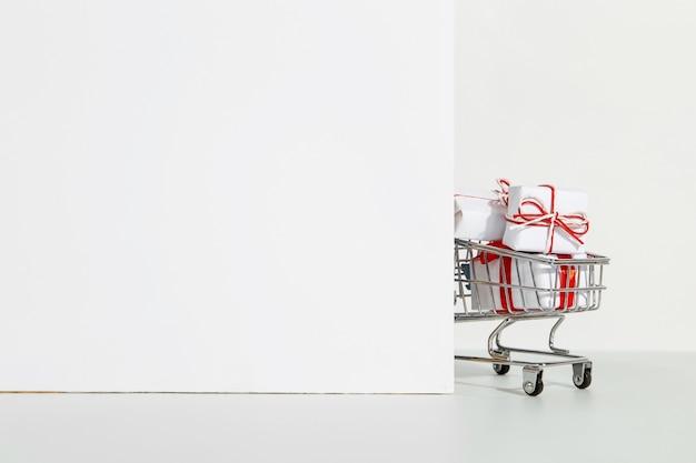 Muchos regalos en el carrito de la compra sobre un fondo blanco.