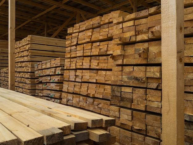 Muchos tablones apilados uno encima del otro en el almacén. madera para su posterior uso en la construcción.