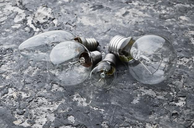 Muchos tipos diferentes de bombillas incandescentes sobre un fondo de hormigón gris. el interior es de estilo loft.