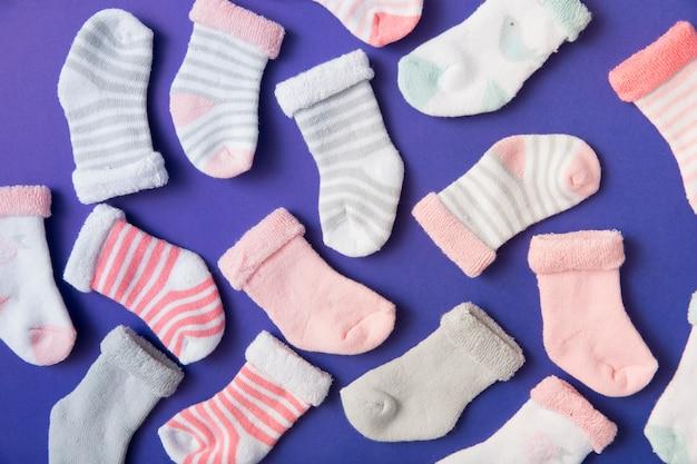 Muchos tipos diferentes de calcetines de bebé sobre fondo azul