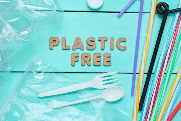 Muchos tubos de cóctel, cuchara de plástico, tenedor, bolsa, botella sobre superficie de madera azul con texto sin plástico