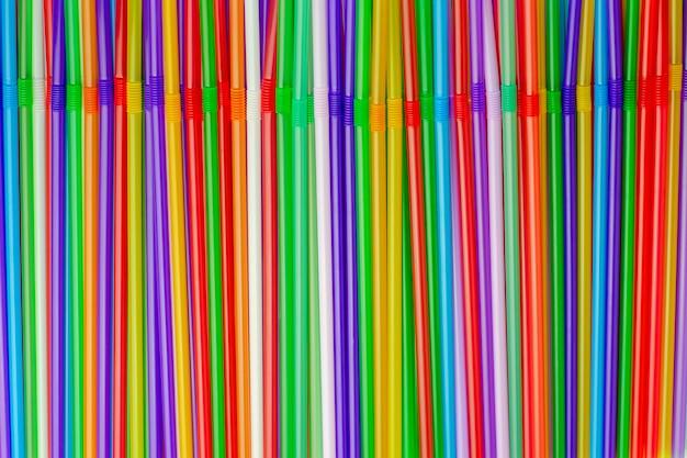 Muchos túbulos de plástico multicolores para jugo o cóctel, desechables de un solo uso. vista superior plana