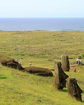 Muchos visitantes en el volcán rano raraku se llenaron con estatuas de moai gigantes sin terminar abandonadas, isla de pascua, chile.