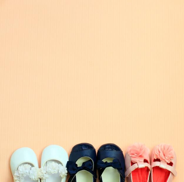 Muchos zapatos de bebé lindo colocados en el fondo de color rosa, vista desde arriba