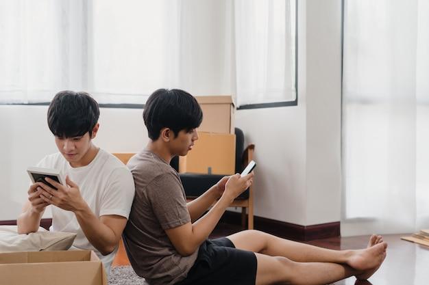 Las mudanzas felices de la reubicación de la pareja gay asiática joven se instalan en un nuevo hogar. asia lover guy lgbtq + caja de cartón abierta o paquete desempacando en la sala de estar el día de la mudanza. vivienda inmobiliaria, préstamo e hipoteca.