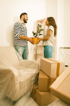 Mudarse, felices hombres y mujeres desempacando cajas, sosteniendo la planta