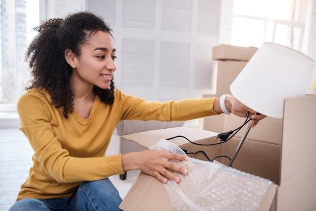 Mudarse. hermosa chica de pelo rizado poniendo una lámpara de mesa en la caja y sonriendo mientras empaca sus pertenencias y se muda a un nuevo piso