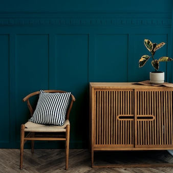 Mueble escandinavo de madera vintage con silla junto a una pared azul oscuro
