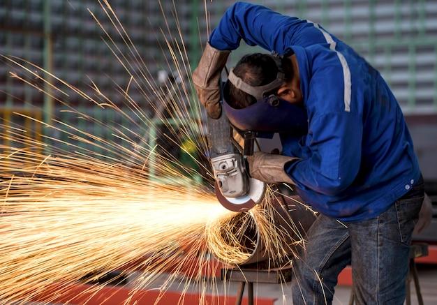 Muela eléctrica de rectificado sobre estructura de acero en fábrica.