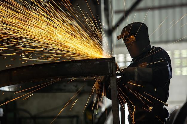 Muela eléctrica de rectificado sobre estructura de acero y soldadores con múltiples chispas en fábrica.