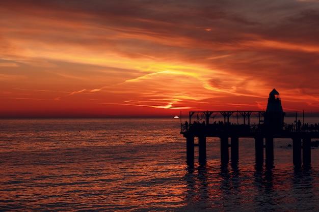 Muelle del faro y puesta de sol sobre el agua