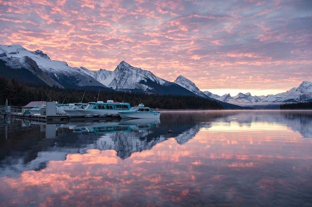 Muelle de ferry y coloridas nubes altocúmulos en el lago maligne en el parque nacional jasper, canadá