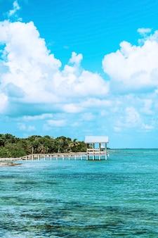 Muelle de madera blanca en mar azul bajo un cielo nublado azul y blanco durante el día