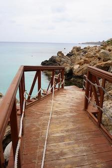 Muelle de madera cerca del océano con una costa rocosa