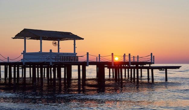 Muelle de madera en una elegante puesta de sol naranja.