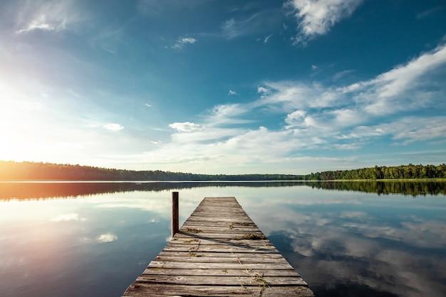 Muelle de madera en el hermoso lago paisaje de amanecer de verano. copie el espacio.