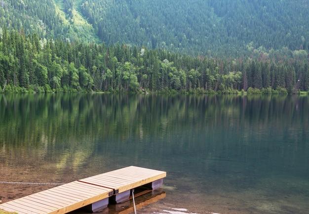 Muelle de madera en el lago de las montañas de serenidad