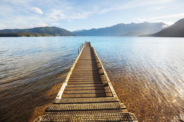 Muelle de madera en el lago de las montañas de la serenidad