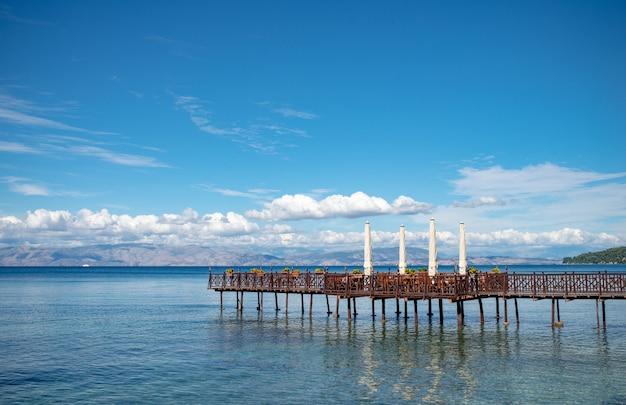 Muelle de madera largo con café romántico al final en el mar jónico.