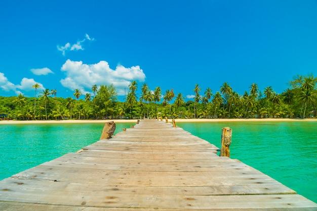 Muelle de madera o puente con playa tropical y mar en isla paradisíaca