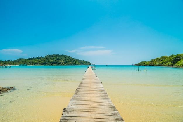 Muelle de madera o puente con playa tropical.