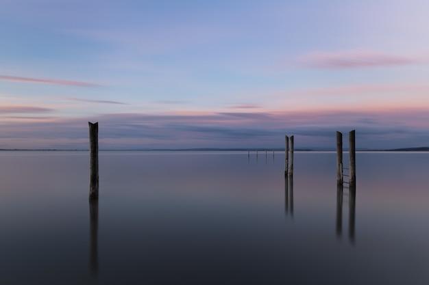 Muelle de madera que se refleja en el mar bajo el hermoso cielo del atardecer